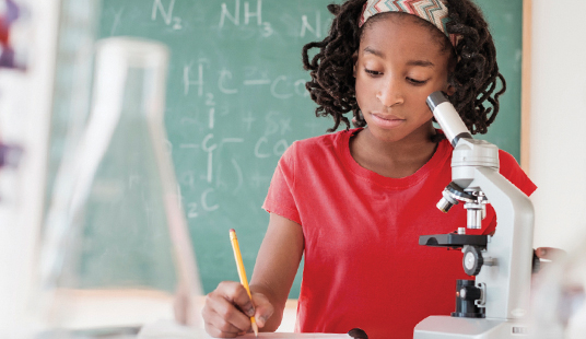 A middle-school African-American girl at a microscope in a classroom science lab writing her notes