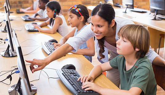 A female teacher working with a diverse group of middle school students in a computer lab
