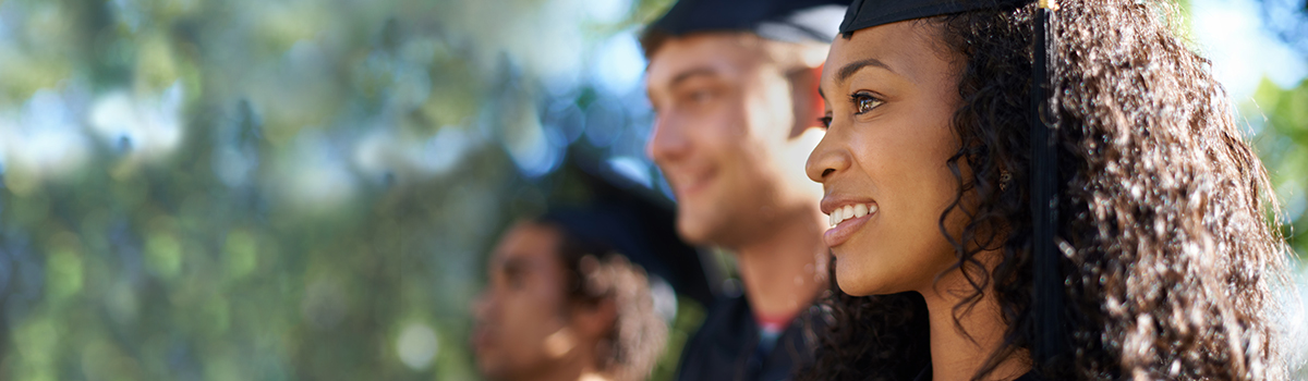 Young woman wearing graduation cap seated outside with other students during sunny, outdoor graduation ceremony.