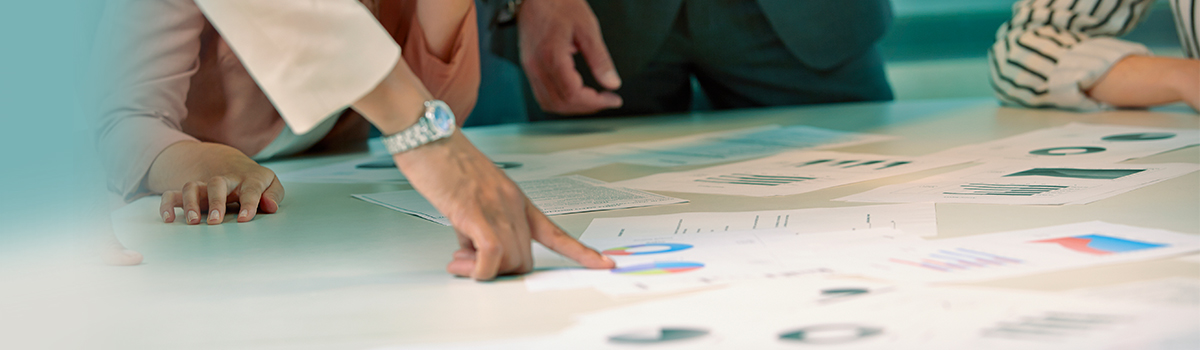 Person pointing at a business plan on the table in a meeting.