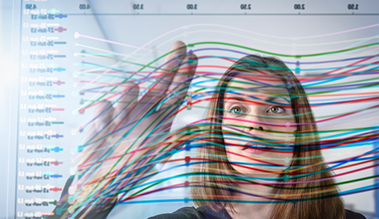 A young woman pointing to lines on a spaghetti graph with many colorful lines
